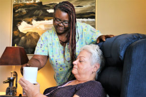 nederland tx senior care provider with long braids smiling and leaning over a client in a chair