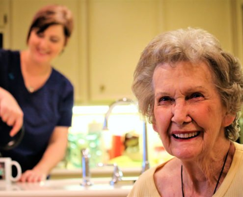 beaumont home health caregiver pours tea for happy senior woman