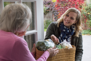 caregiver handing groceries to senior woman